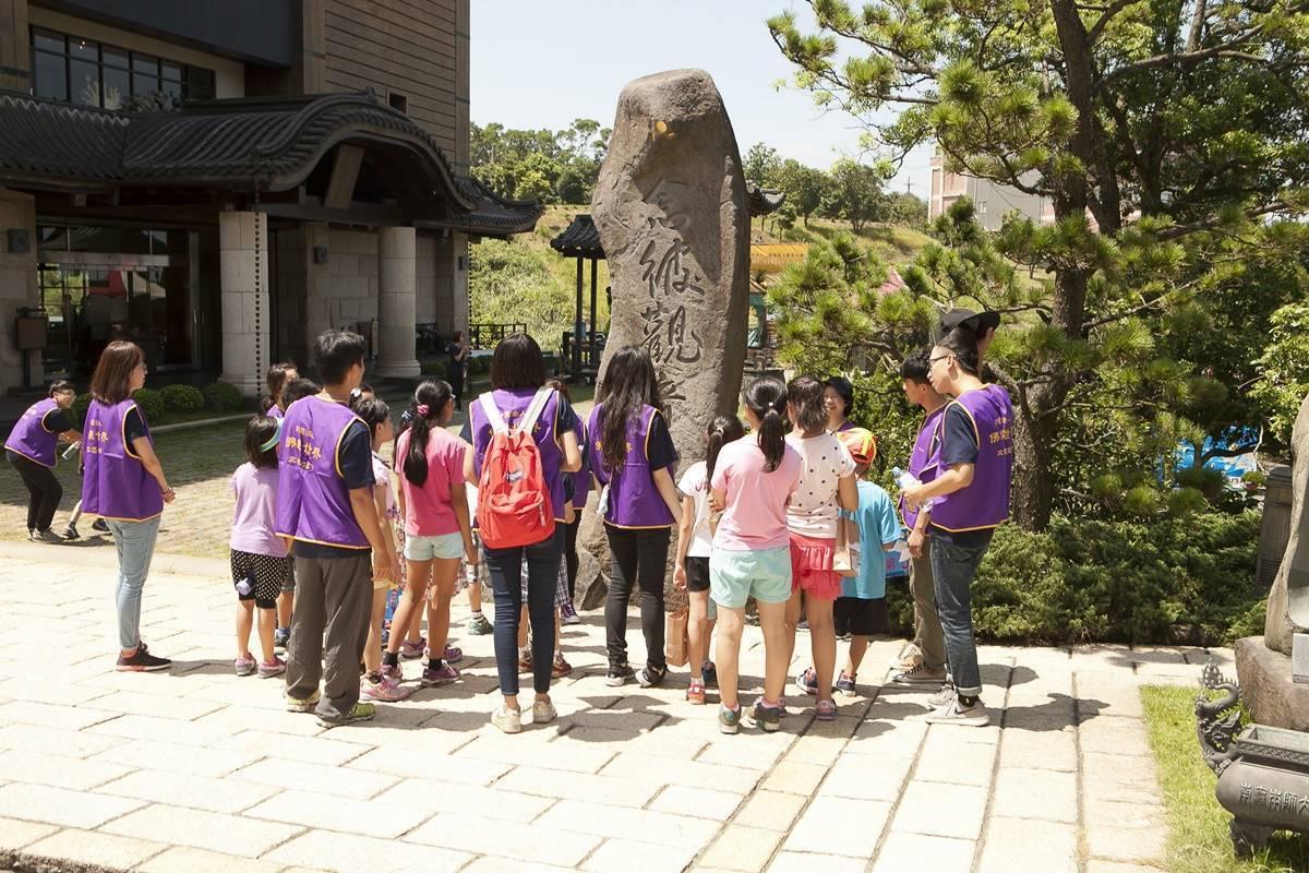 導覽工作人員介紹鎮山石寶「念彼觀音力」,為佛乘宗第三代宗師善單墨寶刻石而成,小朋友們屏氣凝神專注聆聽。