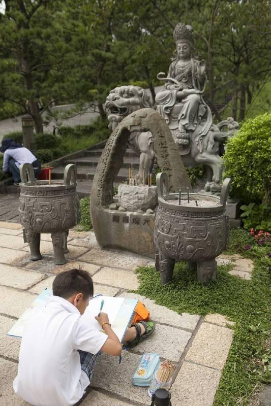 赤子童心藝術夏令營的小朋友坐在「文殊菩薩」前寫生。
