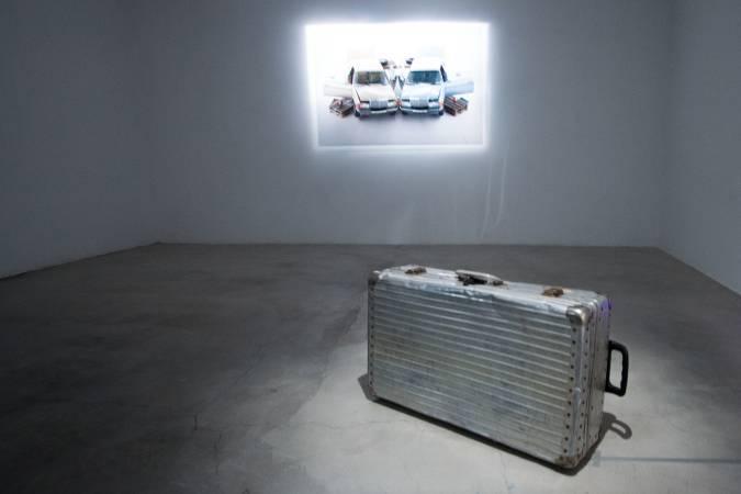 拉納的旅行箱裝置,後方牆上是他作品「汽車系列」照片。圖/ 非池中藝術網攝。