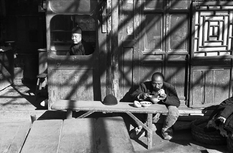 亨利.卡蒂埃.布列松 | 坐在食肆窗內的跑堂或店主,苦力在簷下用餐 北平,1948年12月 明膠銀鹽相紙, 1957 24.8 x 37.3 cm © Fondation Henri Cartier-Bresson / Magnum Photos