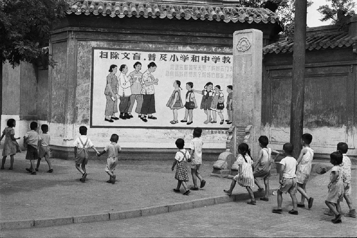 亨利.卡蒂埃.布列松 | 孩童正從一幅寫著「…媽媽們都是上學去…」宣傳標語的看板前經過。 北京,1958年7月 復古式明膠銀鹽相紙, 19.6 x 30 cm © Fondation Henri Cartier-Bresson / Magnum Photos