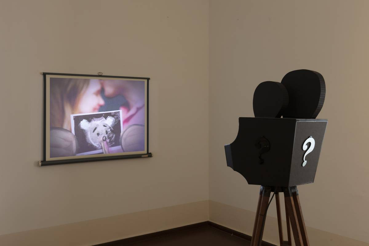 Simon Fujiwara Who's Childhood?, 2021 Sculptural video installation (cardboard, electrical tape, Plexiglas, antique tripod, projector, projection screen, animation, color, sound) 164 x 73 x 73 cm (projector on tripod) Duration: 2:27 min Courtesy the artis